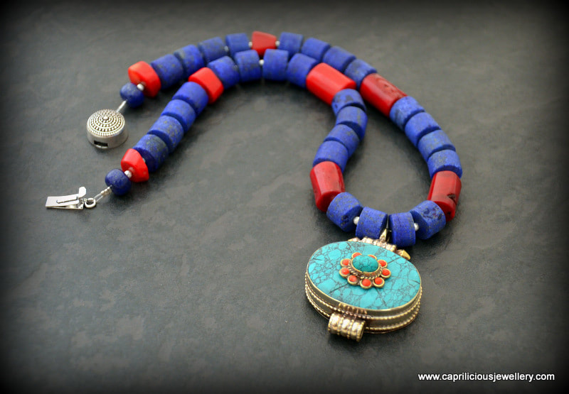 Matte cylinders of lapis lazuli, coral and a turquoise and coral ghau box pendant by Caprilicious Jewellery