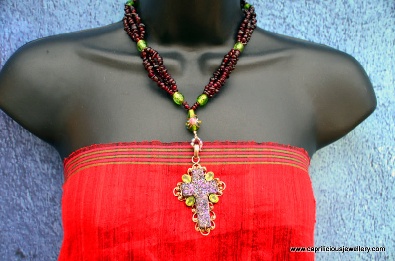 Gothic garnet necklace with a titanium druzy and peridot cross by Caprilicious Jewellery