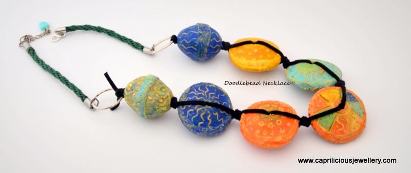 Necklace made with hollow carved polymer clay beads knotted on ultrasuede and Kumihimo by Caprilicious Jewellery