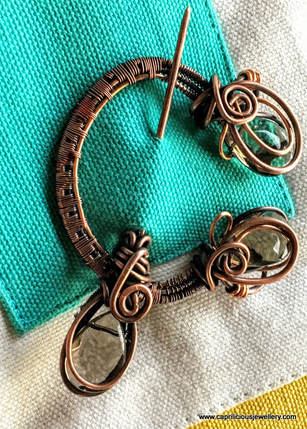 Copper wire penannular brooch by Caprilicious Jewellery